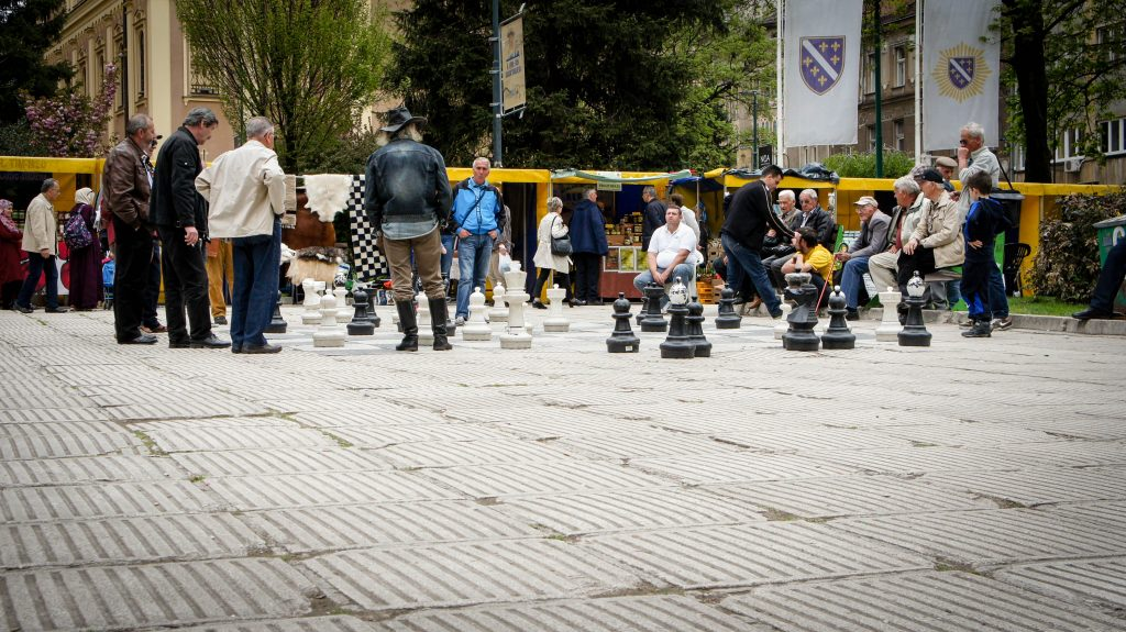 A group of people playing chess in the square.
